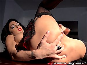 naughty brown-haired Jessica Jaymes fingers her tasty cunt pie in her office